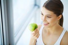 Γυναίκα που τρώει το μήλο Όμορφο κορίτσι με τα άσπρα δόντια που δαγκώνουν τη Apple Στοκ Φωτογραφίες