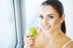 Γυναίκα που τρώει το μήλο Όμορφο κορίτσι με τα άσπρα δόντια που δαγκώνουν τη Apple Στοκ εικόνες με δικαίωμα ελεύθερης χρήσης