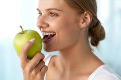 Γυναίκα που τρώει το μήλο Όμορφο κορίτσι με τα άσπρα δόντια που δαγκώνουν τη Apple Στοκ Εικόνες