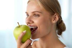 Γυναίκα που τρώει το μήλο Όμορφο κορίτσι με τα άσπρα δόντια που δαγκώνουν τη Apple Στοκ Εικόνα