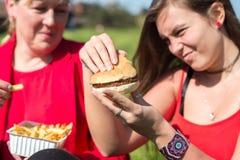Γυναίκα που τρώει το χάμπουργκερ και τις τηγανιτές πατάτες Στοκ Εικόνες