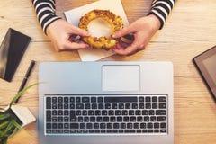 Γυναίκα που τρώει bagel σουσαμιού για το πρόγευμα στην αρχή, τη τοπ άποψη Στοκ Φωτογραφίες