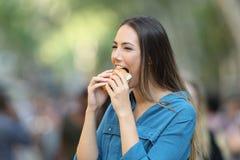 Γυναίκα που τρώει burger στην οδό στοκ εικόνες