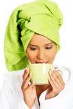 Γυναίκα που τυλίγεται ελκυστική στην πετσέτα με το τουρμπάνι στο κεφάλι, που κρατά το α Στοκ φωτογραφία με δικαίωμα ελεύθερης χρήσης