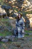 Γυναίκα που τυλίγεται στη γενική συνεδρίαση σε έναν βράχο Στοκ Εικόνα