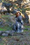 Γυναίκα που τυλίγεται στη γενική συνεδρίαση σε έναν βράχο Στοκ εικόνες με δικαίωμα ελεύθερης χρήσης