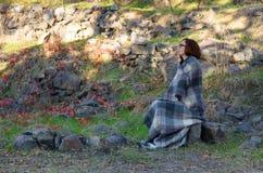 Γυναίκα που τυλίγεται στη γενική συνεδρίαση σε έναν βράχο Στοκ Φωτογραφία