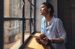 Γυναίκα που υπερασπίζεται το παράθυρο γραφείων με την ψηφιακή ταμπλέτα Στοκ φωτογραφίες με δικαίωμα ελεύθερης χρήσης