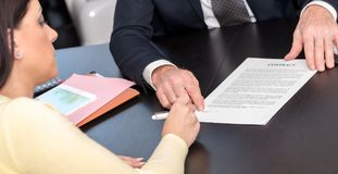 Γυναίκα που υπογράφει τη σύμβαση με τον οικονομικό σύμβουλο Στοκ Φωτογραφία