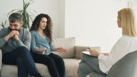 γυναίκα που υποστηρίζει και που μιλά για το σύζυγό της στο σύμβουλοη γάμου Νέο ζεύγος που επισκέπτεται τον επαγγελματικό ψυχολόγο απόθεμα βίντεο
