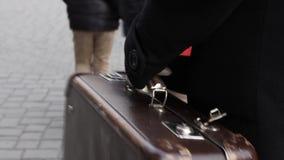Γυναίκα που φέρνει μια εκλεκτής ποιότητας βαλίτσα απόθεμα βίντεο