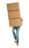 Γυναίκα που φέρνει τα συσσωρευμένα κουτιά από χαρτόνι στεμένος σε ένα πόδι στοκ εικόνα