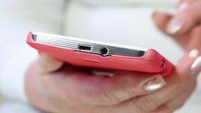 Γυναίκα που φαίνεται οι φωτογραφίες στο smartphone της Γυναίκα που κρατά ένα κόκκινο τηλέφωνο κυττάρων φιλμ μικρού μήκους