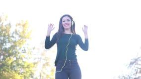 Γυναίκα που φορά τα ακουστικά και το χορό, που στέλνουν το φιλί στη κάμερα απόθεμα βίντεο