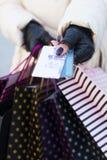 Γυναίκα που φορά τα γάντια που παρουσιάζουν πιστωτικές κάρτες Στοκ Φωτογραφίες