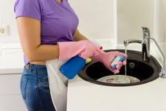 Γυναίκα που φορά τα γάντια που πλένουν τα πιάτα Στοκ Εικόνα