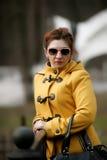 Γυναίκα που φορά τα γυαλιά ηλίου και ένα κίτρινο παλτό Στοκ Εικόνες