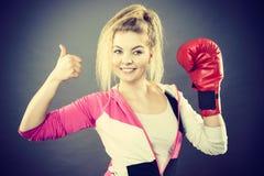 Γυναίκα που φορά τα εγκιβωτίζοντας γάντια που παρουσιάζουν αντίχειρα Στοκ Εικόνα
