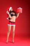 Γυναίκα που φορά τα ενδύματα Άγιου Βασίλη με το δώρο Χριστουγέννων στοκ φωτογραφία με δικαίωμα ελεύθερης χρήσης