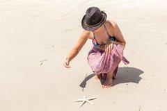 Γυναίκα που φορά την άμμο παραλιών γραψίματος μαύρων καπέλων Στοκ φωτογραφία με δικαίωμα ελεύθερης χρήσης