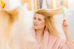 Γυναίκα που φορά την εσθήτα επιδέσμου που βουρτσίζει την τρίχα της Στοκ Εικόνες