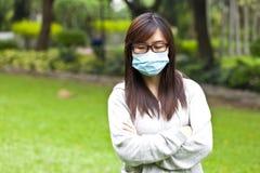 Γυναίκα που φορά την προστατευτική μάσκα προσώπου στο πάρκο Στοκ εικόνα με δικαίωμα ελεύθερης χρήσης