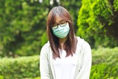 Γυναίκα που φορά τη μάσκα στο πάρκο Στοκ Φωτογραφία