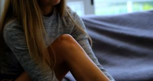 Γυναίκα που φορά τις κάλτσες στον καναπέ 4k απόθεμα βίντεο