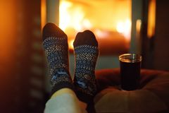Γυναίκα που φορά τις μάλλινες κάλτσες κοντά στην εστία Χριστουγέννων στοκ φωτογραφίες
