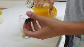 Γυναίκα που φορά τις πυτζάμες που παίρνουν το χυμό από πορτοκάλι από το ψυγείο φιλμ μικρού μήκους