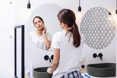 Γυναίκα που φορά τις συμπαθητικές comfy πυτζάμες που φροντίζουν το δέρμα της στοκ εικόνες με δικαίωμα ελεύθερης χρήσης