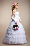 Γαμήλιο ύφος. Νύφη που φορά το άσπρα φόρεμα και τα γάντια. Καθιερώνουσα τη μόδα ανθοδέσμη των λουλουδιών Στοκ Εικόνες