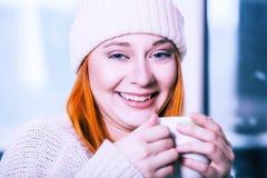 Γυναίκα που φορά το θερμό ιματισμό και που πίνει το ζεστό ποτό Στοκ εικόνες με δικαίωμα ελεύθερης χρήσης