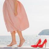 Γυναίκα που φορά το μακρύ ανοικτό ροζ φόρεμα στο λιμενοβραχίονα στοκ φωτογραφία με δικαίωμα ελεύθερης χρήσης