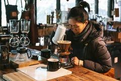 Γυναίκα που φορά το παλτό και που κατασκευάζει χύνω-πέρα τον καφέ με την εναλλακτική μέθοδο αποκαλούμενη στάλαγμα στοκ φωτογραφία