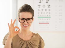 Γυναίκα που φορά eyeglasses που παρουσιάζουν εντάξει χειρονομία κοντά στο διάγραμμα Snellen Στοκ Φωτογραφία