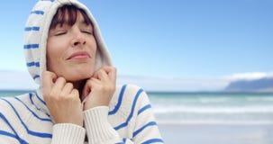 Γυναίκα που φορά hoodie στην παραλία απόθεμα βίντεο