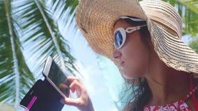 Γυναίκα που φορούν τα γυαλιά ηλίου και καπέλο που χρησιμοποιούν το τηλέφωνο app στην παραλία στις διακοπές θερινού ταξιδιού κίνησ απόθεμα βίντεο