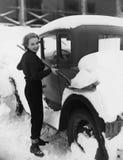 Γυναίκα που φτυαρίζει το χιόνι από το αυτοκίνητο (όλα τα πρόσωπα που απεικονίζονται δεν ζουν περισσότερο και κανένα κτήμα δεν υπά Στοκ εικόνα με δικαίωμα ελεύθερης χρήσης