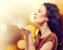 Γυναίκα που φυσά τη μαγική σκόνη στοκ εικόνες