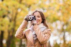 Γυναίκα που φωτογραφίζει με τη κάμερα στο πάρκο φθινοπώρου Στοκ φωτογραφία με δικαίωμα ελεύθερης χρήσης