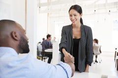Γυναίκα που χαιρετά έναν μαύρο επιχειρηματία σε μια συνεδρίαση των γραφείων Στοκ Εικόνες
