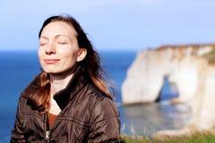 Γυναίκα που χαμογελά κάνοντας τις ασκήσεις αναπνοής πάνω από τους απότομους βράχους της Νορμανδίας την άνοιξη στοκ φωτογραφία