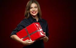 Γυναίκα που χαμογελά με τα δόντια που κρατούν το κόκκινο κιβώτιο δώρων Στοκ φωτογραφία με δικαίωμα ελεύθερης χρήσης