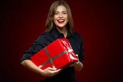 Γυναίκα που χαμογελά με τα δόντια που κρατούν το κόκκινο κιβώτιο δώρων Στοκ Εικόνες