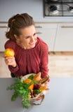 Γυναίκα που χαμογελά και που κρατά τα λαχανικά μήλων και πτώσης στην κουζίνα Στοκ Φωτογραφία