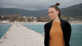 Γυναίκα που χαμογελά και που στέκεται σε μια μακριά αποβάθρα στη θάλασσα στο νεφελώδη καιρό απόθεμα βίντεο
