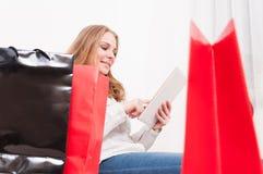 Γυναίκα που χαμογελά και που ψωνίζει on-line με τις τσάντες arround Στοκ Εικόνα