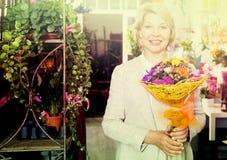 Γυναίκα που χαμογελά μεταξύ των πολύχρωμων λουλουδιών Στοκ φωτογραφία με δικαίωμα ελεύθερης χρήσης