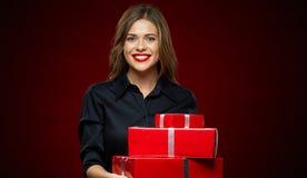 Γυναίκα που χαμογελά με τα δόντια που κρατούν το κόκκινο κιβώτιο δώρων Στοκ Φωτογραφίες